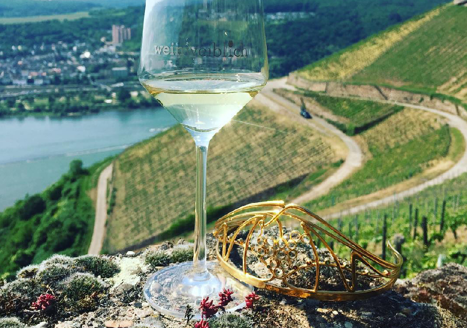 A glass of german white wine in the foreground with a steep slope of vineyard in the distance