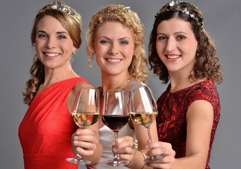 Crowned wine queens holding up three glasses of wine